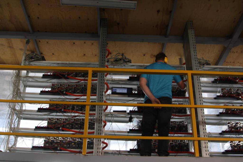 ビットリバーのマイニング施設でマシンをチェックするエンジニア。